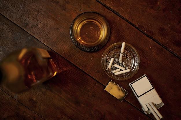 Сигарета в пепельнице и алкогольный напиток в бутылке на деревянном столе, вид сверху. культура табакокурения, специфический аромат. концепция вредных привычек