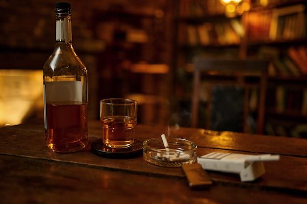 재떨이에 있는 담배와 나무 탁자에 있는 알코올 음료, 아무도. 담배 흡연 문화, 배경에 빈티지 사무실 인테리어. 특정 맛. 흡연 습관