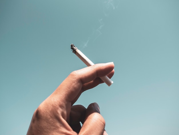 Cigarette in man hand with smoke on blue sky wall. hand holding cigarette.