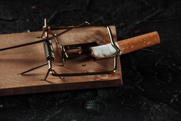 Cigarette on a mouse trap close-up. dangerous habbit concept