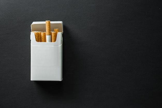 Сигарета на темной поверхности. пепельница. бросить курить
