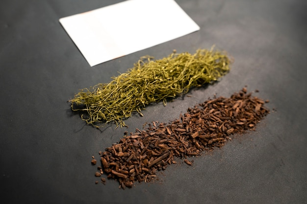 Cigarette paper and pile of tobacco on black background