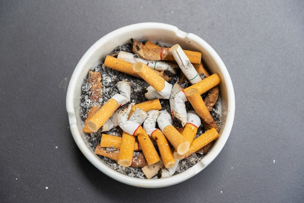 Cigarette stub in the ashtray on the table