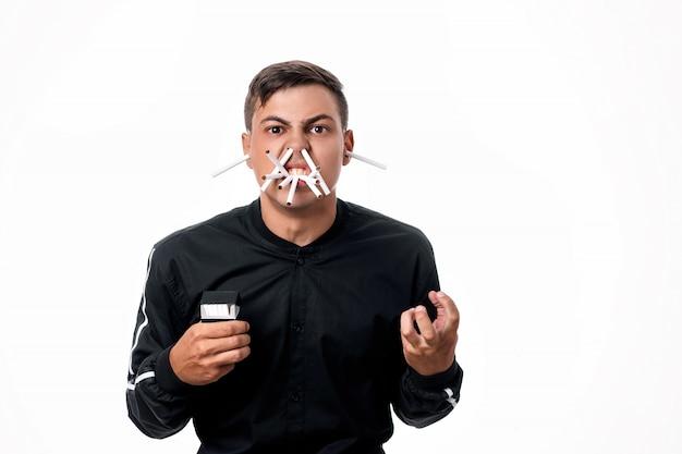 Сигареты есть везде. молодой человек с гневом к курению. на его лице сигареты повсюду - в носу, во рту, в ушах. курение убивает. он сжимает кулак в гневе. изолированные