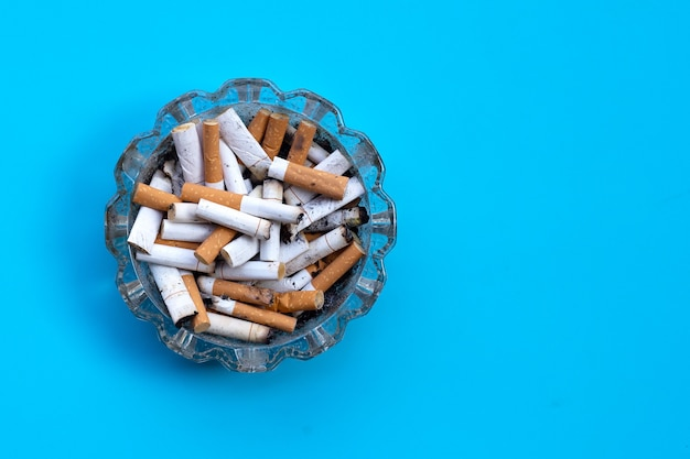 Cigarettes buds in a transparent ashtray on blue.