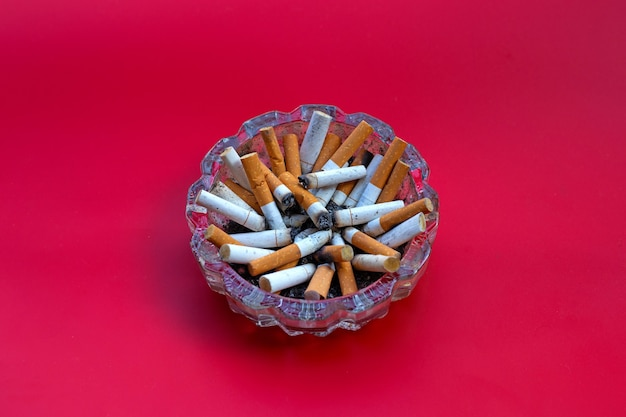 Cigarettes buds in a transparent ashtray on red space.