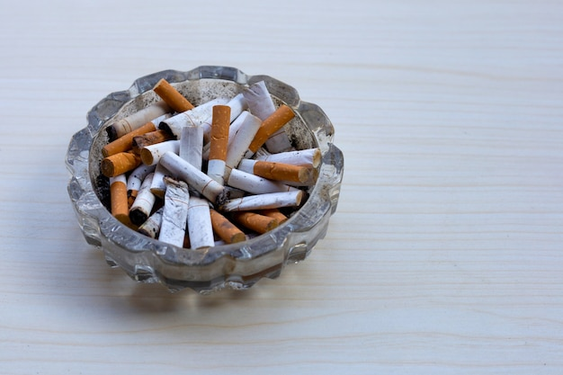 Cigarettes buds in a transparent ashtray on table