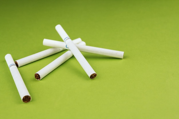 Cigarettes on a green background copy space. a few cigarettes.