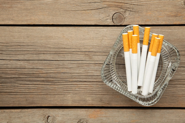灰色の木製テーブルに灰皿のタバコ。上面図。