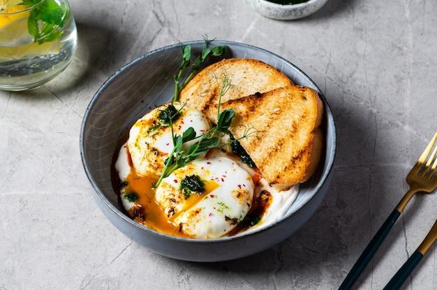 킬비르 또는 터키식 달걀. 메제(mezze)로 제공되는 요리: 데친 달걀을 허브 그리스 요구르트 위에 얹은 다음 매운 파프리카 올리브 오일을 뿌립니다. 대리석 배경의 회색 그릇에 담긴 터키식 아침 식사