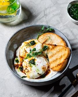 Цильбир или турецкие яйца. блюдо служило меззе: яйца-пашот, посыпанные греческим йогуртом с травами, затем сбрызнутые горячим приправленным пряностями оливковым маслом паприки. турецкий завтрак в серой миске на мраморном фоне