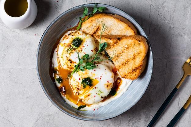킬비르 또는 터키식 달걀. 메제(mezze)로 제공되는 요리: 데친 달걀을 허브 그리스 요구르트 위에 얹은 다음 매운 매운 파프리카 올리브 오일을 뿌립니다. 대리석 배경의 회색 그릇에 담긴 터키식 아침 식사