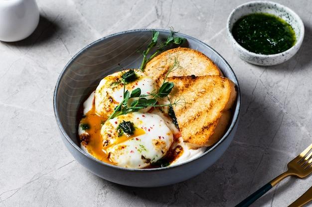 킬비르 또는 터키식 달걀. 허브 그릭 요거트 위에 데친 달걀을 얹고 매운 파프리카 올리브 오일을 뿌립니다. 대리석 배경에 회색 그릇에 터키식 아침 식사. 후추를 곁들인 샤크슈카.
