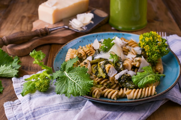 Cime di rapa pasta in a plate on with parmesan on a wooden table. traditional food of the south of italy, from puglia. rustic style photo. copy space