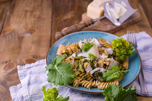 Cime di rapa pasta in a plate on with parmesan on a wooden table. traditional food of the south of italy, from puglia. rustic style photo.