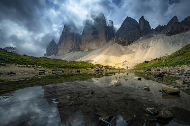 Красивый взгляд ландшафтов отражения горы на реке с голубым небом на лете от cime tre, доломитах, италии.