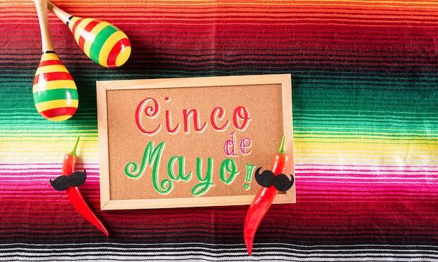 メキシコのブランケットストライプまたはポンチョにマラカスと唐辛子から作られたシンコデマヨの休日の背景