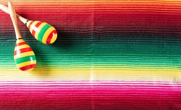 メキシコのブランケットストライプまたはポンチョの背景にマラカスから作られたシンコデマヨの休日の背景