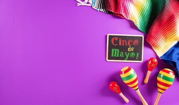 マラカスメキシコのブランケットストライプまたはポンチョから作られたシンコデマヨの休日の紫色の背景