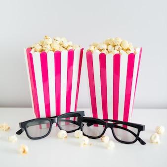 영화 및 날짜 개념 - 팝콘과 3d 안경이 있는 두 개의 빨간색 줄무늬 상자