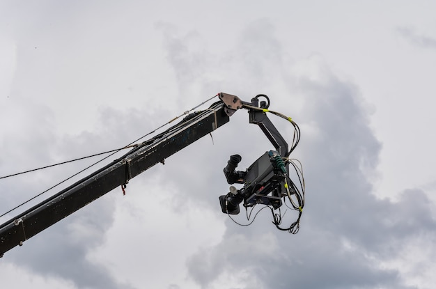 Кино- и телеаппарат подвешен на телескопическом кране на фоне облачного неба.