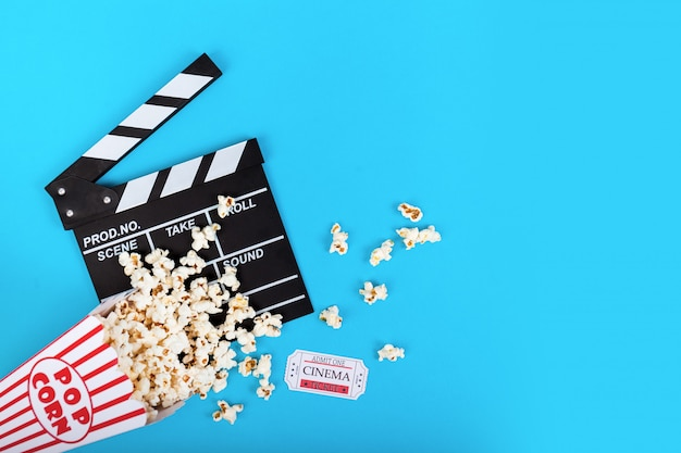 Cinema background. popcorn and clapperboard on blue