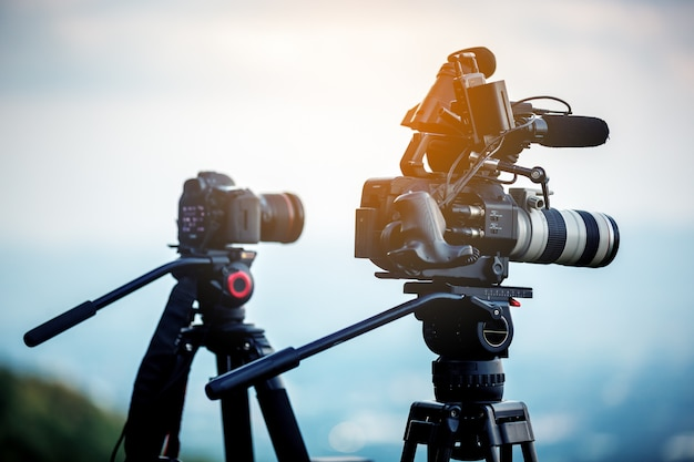 Cinema camera on tripod in sunset , video production concept