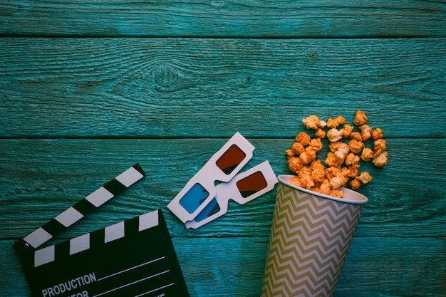 Cinema concept. clapperboard, glasses and popcorn on blue wooden table, top view