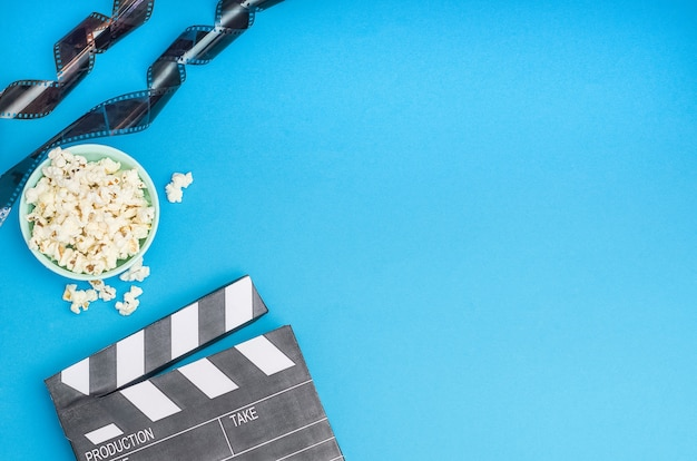 Cinema concept - clapperboard with popcorn and film strip on blue background with copy space.