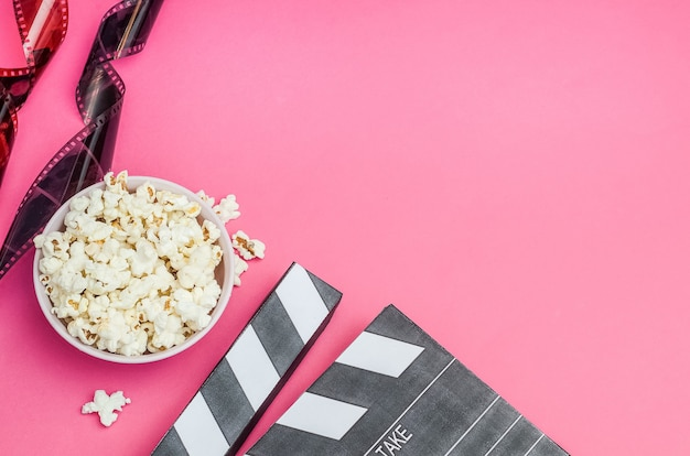 Cinema concept - clapperboard with popcorn and film strip on pink background with copy space.
