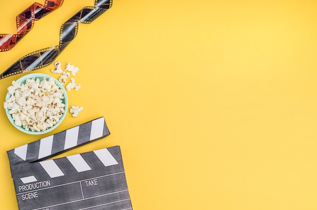 Cinema concept - clapperboard with popcorn and film strip on yellow background with copy space.