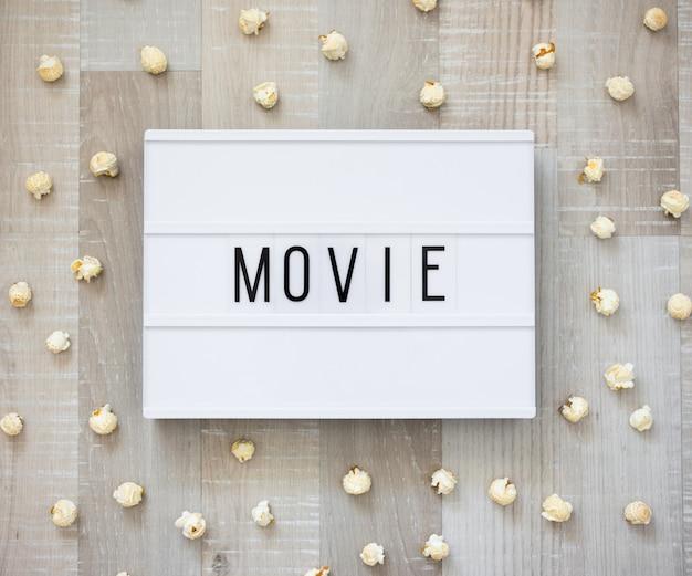 영화 개념 - 나무 배경 위에 영화 단어와 팝콘이 있는 복고풍 라이트 박스