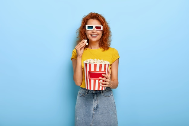 Cinema day and free time concept. young optimistic red haired happy woman has fun while watches interesting movie