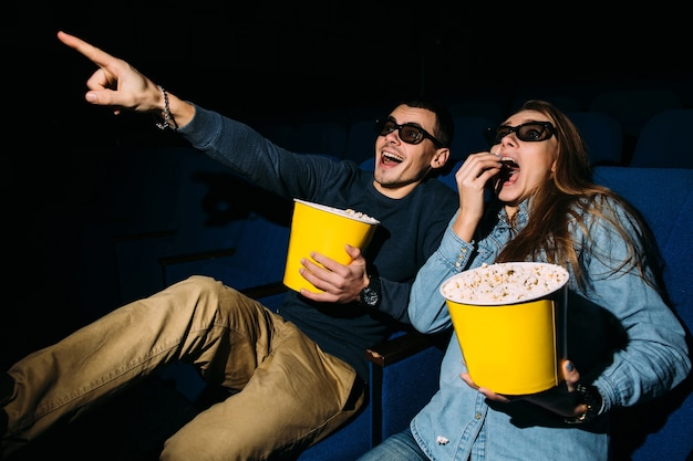 Cinema day, young couple with popcorn looking action movie in cinema.