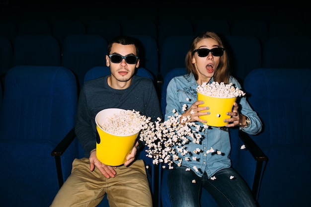 영화의 날. 영화관에서 그들의 날짜에 흥미로운 영화를보고 팝콘과 젊은 부부.