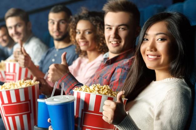 Любители кино все здесь. группа веселых друзей, показывая пальцы вверх вместе, сидя в кинотеатре