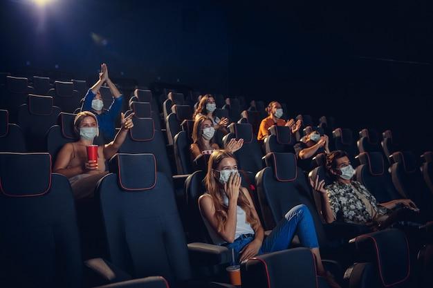 Кино на карантине. правила безопасности при пандемии коронавируса, социальная дистанция при просмотре фильмов. мужчины, женщины в защитных масках сидят в рядах зрительного зала. свободное время, концепция молодежной культуры.