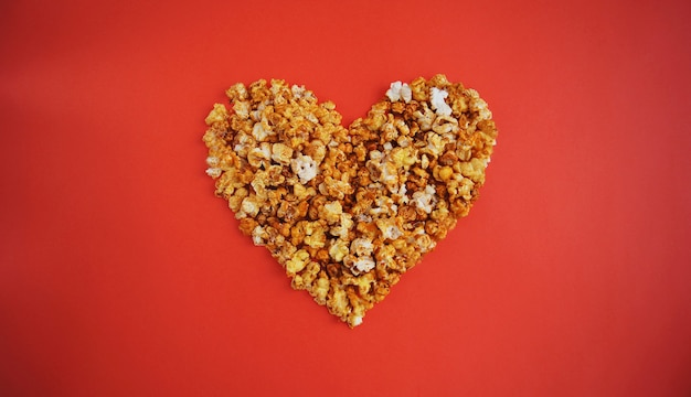 Cinema lovers concept of popcorn. heart shaped white fluffy popcorn on red wall. valentine´s day