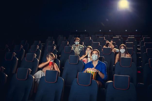 검역 중 영화관, 영화관. 코로나바이러스 전염병 안전 규칙, 영화 감상 중 사회적 거리. 보호용 안면 마스크를 쓰고 강당에 앉아 포를 먹는 남녀