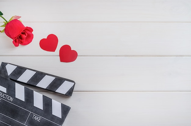 バレンタインデーの映画館。映画広告。白い木製の背景にハートとバラのシネマカチンコ。ロマンティックな映画。