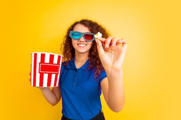 映画のテーマ、ポップコーンを食べる。黄色の壁に白人の十代の少女の肖像画。美しい女性の巻き毛モデル。人間の感情、表情、販売、広告、教育の概念。コピースペース。