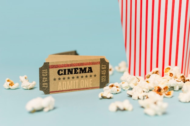 Cinema ticket near the popcorns against blue background