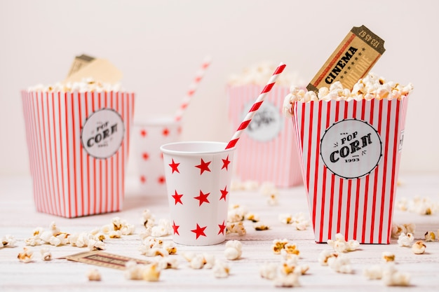 Cinema ticket in the popcorns box with drinking glass and straw on wooden table