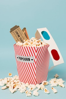 Cinema tickets and 3d glasses on popcorn box against blue background