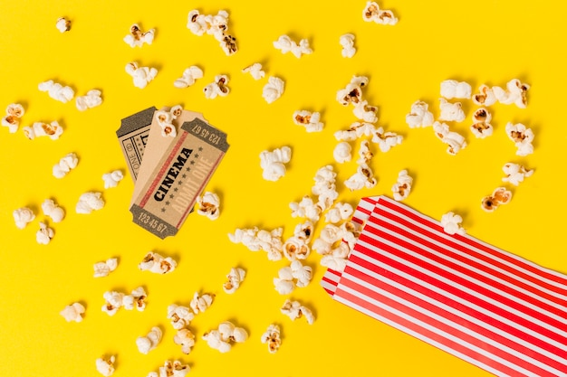 Cinema tickets over the spilled popcorns against yellow backdrop