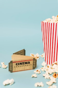 Cinema tickets with popcorns against blue backdrop