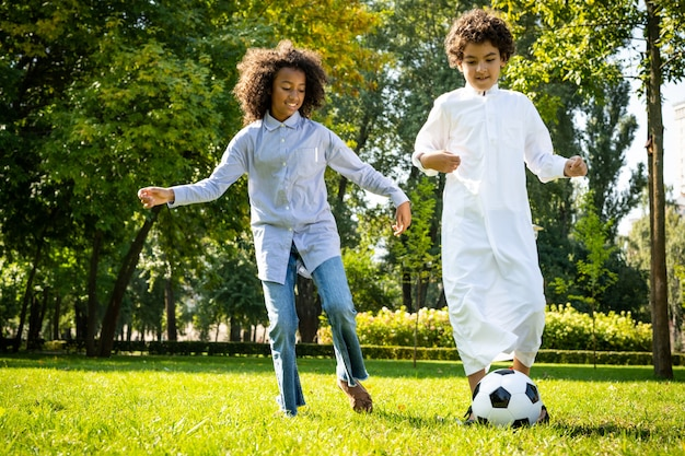 공원에서 시간을 보내는 에미레이트 항공의 가족의 영화적 이미지. 잔디에서 축구를 하는 형제와 자매