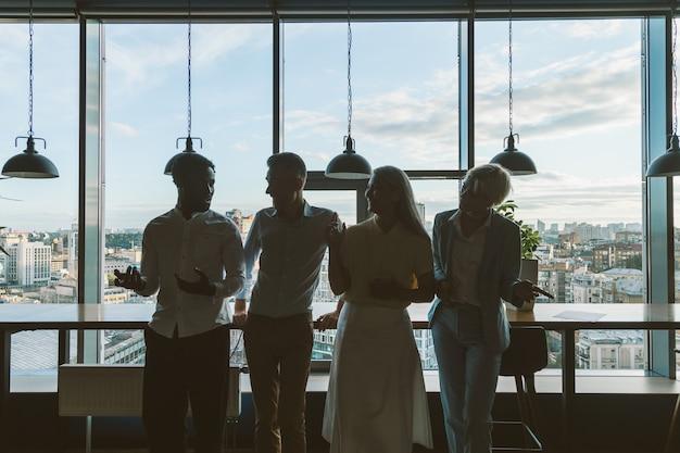 Кинематографический образ многонациональной деловой команды. сотрудники разговаривают на балконе во время перерыва