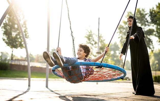 놀이터에서 아이들과 즐거운 시간을 보내는 에미레이트 항공의 한 여성의 영화적 이미지