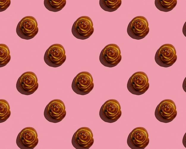 분홍색 배경 패턴에 계피 롤빵